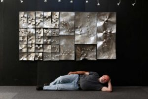 Alain Vuillemet devant le relief en hommage à Zoltan Kemeny Space in Order, valoriser vos événements avec la sculpture