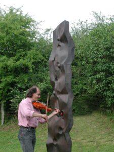 Jean Marc Ladet au violon devant la sculpture Supergravitation pour le concert au château